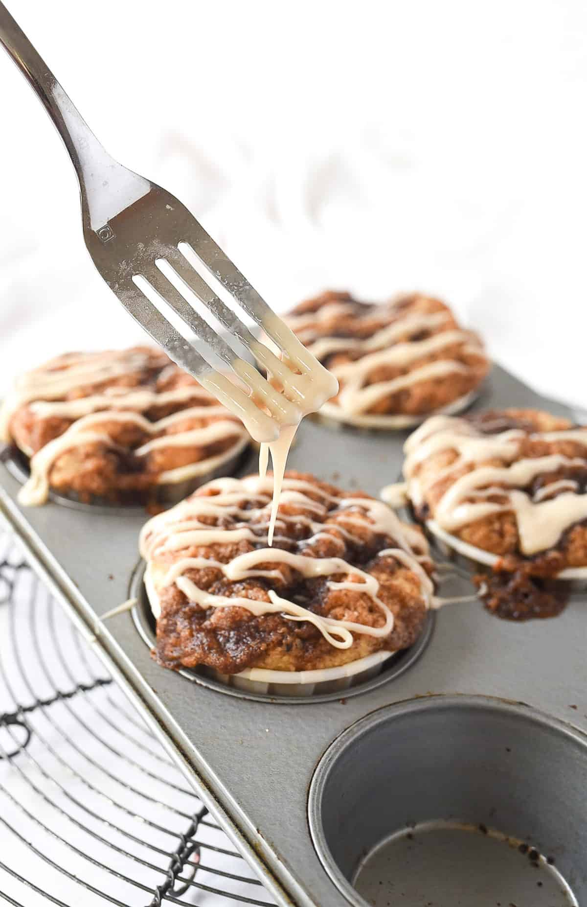 drizzling cinnamon roll muffins with glaze