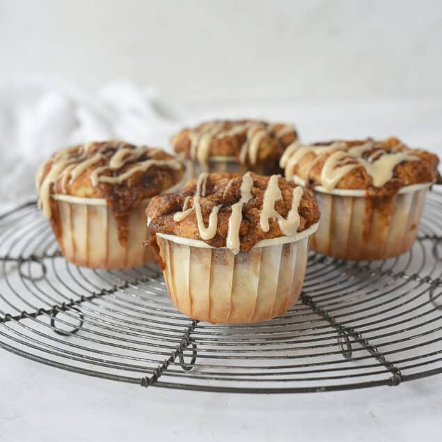 four cinnamon roll muffins on a cooling rack